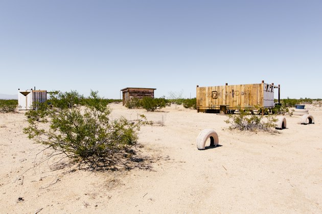 a view across scrubby desert of three rustic wooden buildings