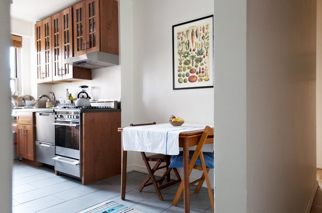 Wooden dining room table in a small kitchen with stove vent