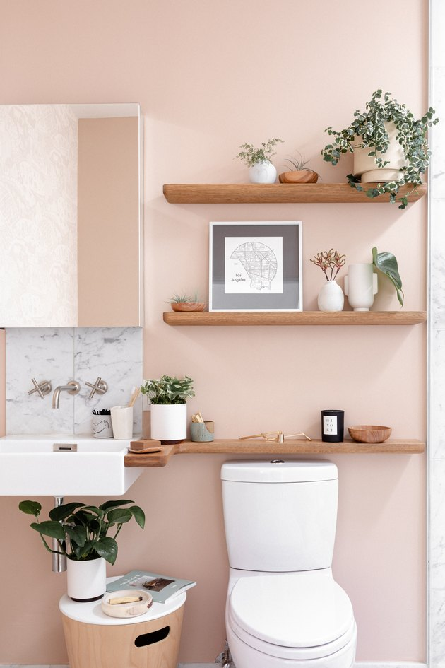three wooden floating shelves above a toilet