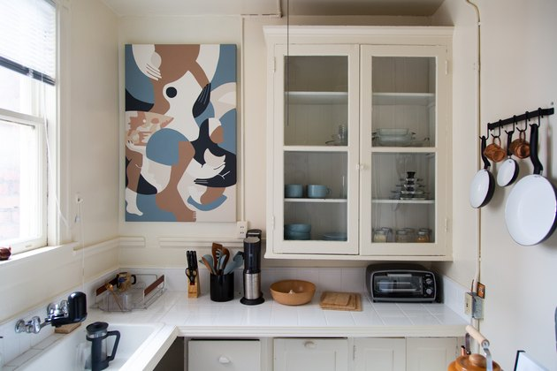 White kitchen counter with windowed shelving unit and pots and pans hanging over stove