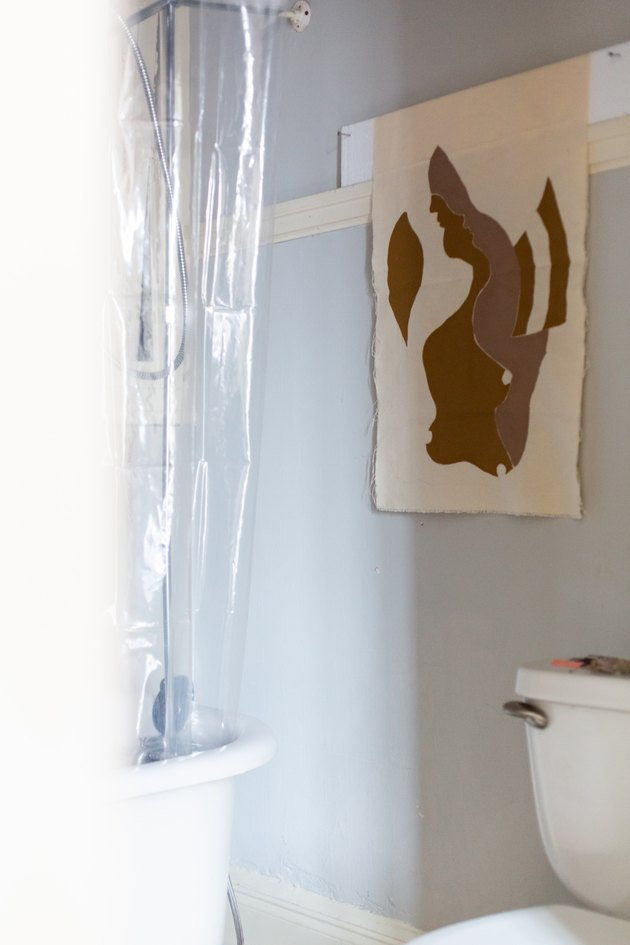 Bathroom with toilet and clear shower curtain with artwork on wall