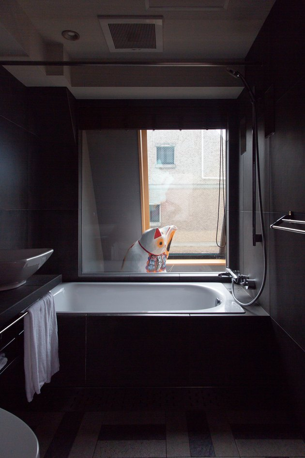 a deep white tub contrasts with dark gray walls and floor; a waving lucky cat figurine is visible through the bathroom window