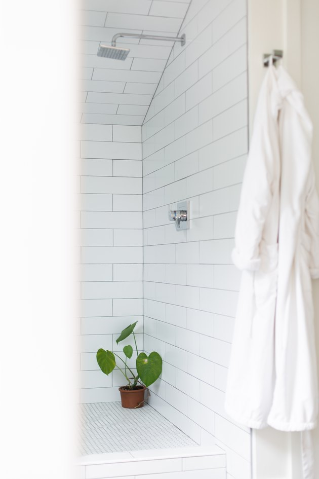 white subway tile shower, silver overhead showerhead, potted plant in the corner of the shower, white bathrobe hung up