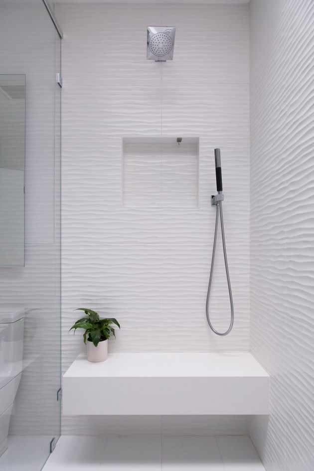 white shower with bench that has a small plant on it, glass door, overhead showerhead and handheld showerhead
