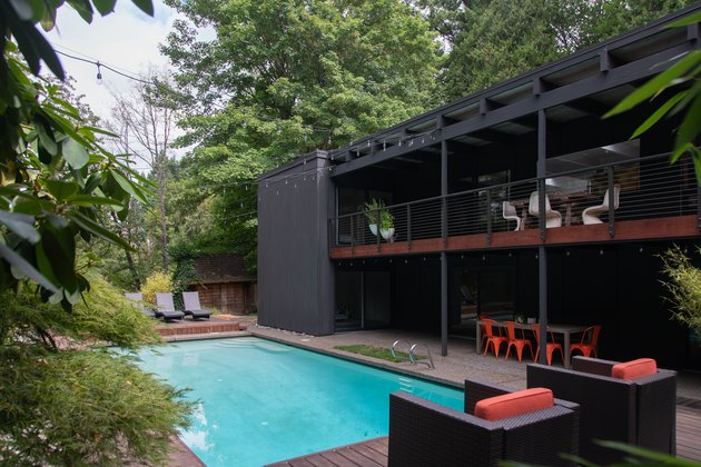 A two-story midcentury home with a rectangular in-ground pool surrounded by patio furniture