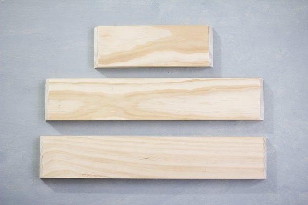 Three plywood panels against grey background