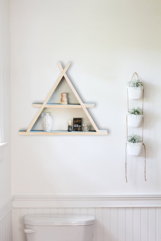 Wooden a-frame shelf holding small containers on white wall next to hanging succulent wall-holder