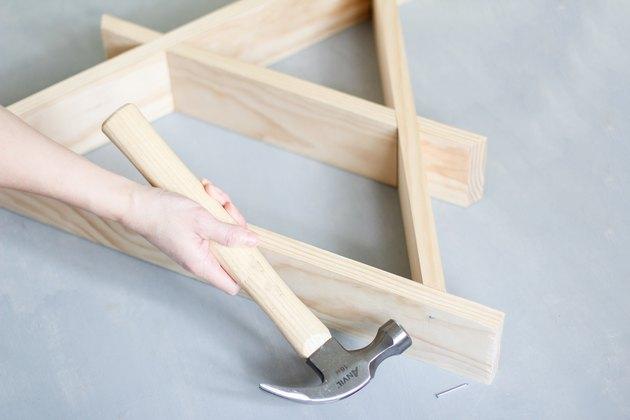 Hand hammering together wooden a-frame shelf against grey background