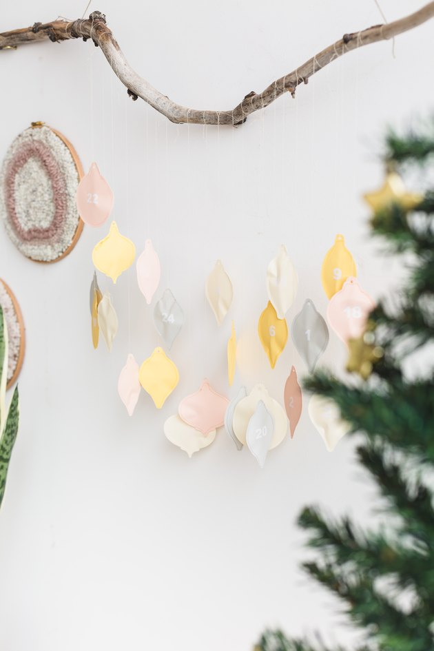 a diy advent calendar with colorful hand-sewn numbered charms shaped like christmas lights, hanging from a tree branch