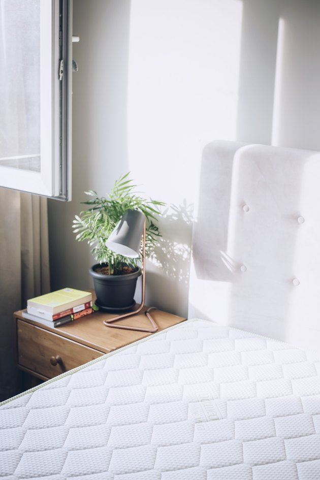 White mattress next to side table with lamp and plant in white-walled room with white curtains