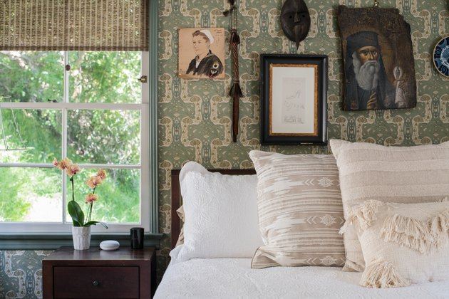 white linen bed with wallpaper and vintage photos behind it