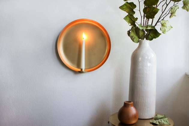 Round sconce with candle next to white vase with plant