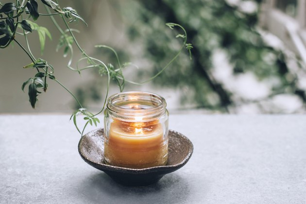 a diy beeswax candle burning in a glass jar on a saucer