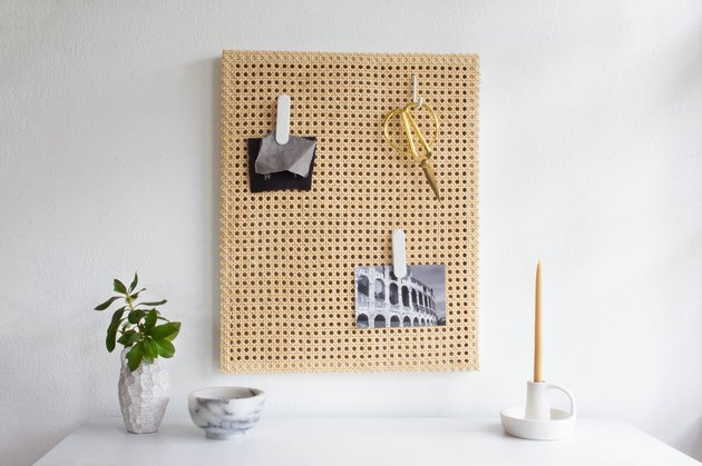 Cane memo board with scissors and photos over white desk with plant and candle