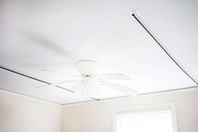 a ceiling fan between two curtain rods suspended from the ceiling with stick-on hooks