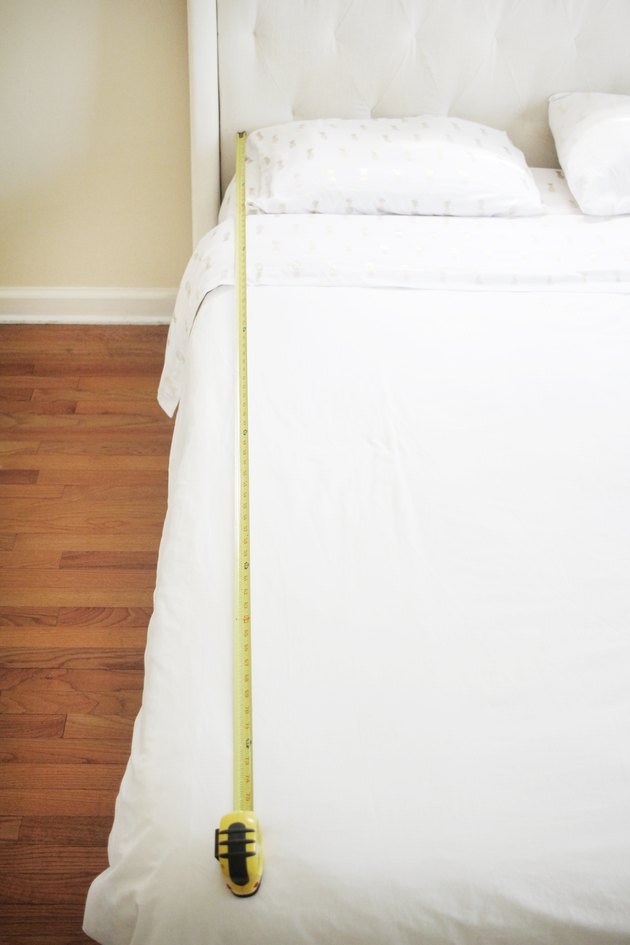 using a measuring tape to measure the length of an all-white bed