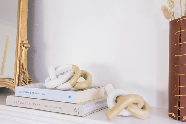 Decorative clay knots on mantel with books, leather vase and gold mirror
