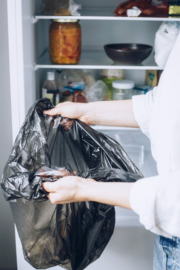 Hand holding black garbage bag in front of fully stocked white refrigerator