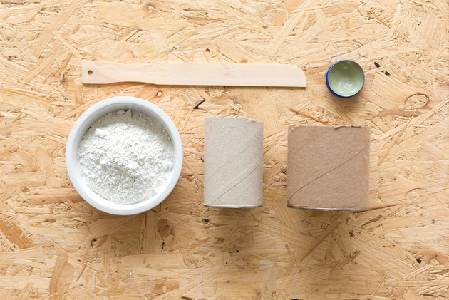 Paint mixer, wax, powder concrete, two cylindrical cardboard containers on wood tabletop
