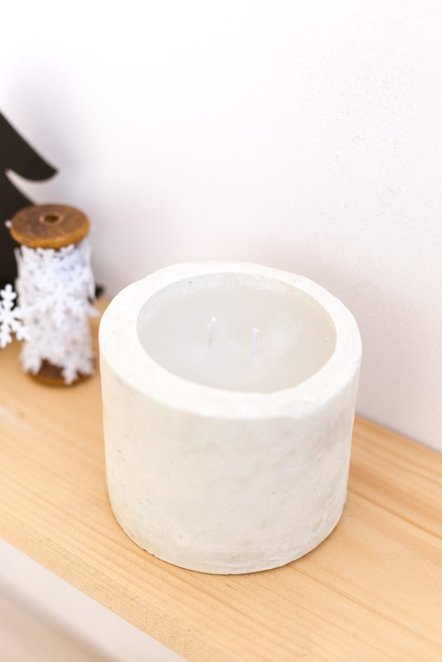 DIY concrete candle on wooden ledge next to snowflake string against white background