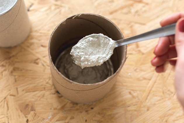Hand mixing concrete with metal spoon in cylindrical cardboard container on wood countertop