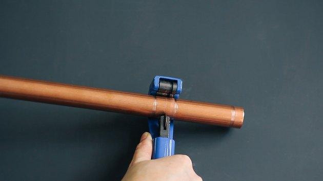 using a pipe cutter to trim copper pipe