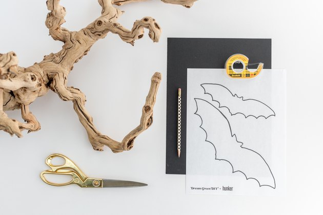 a bare branch, scissors, black construction paper, tape, a pencil, and bat cut-out templates