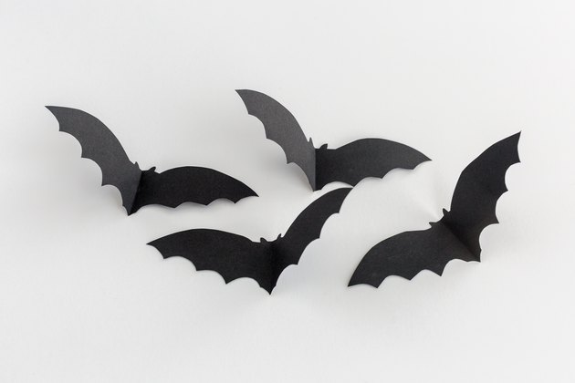 black paper bat cut-outs creased in the middle to look like they're flying