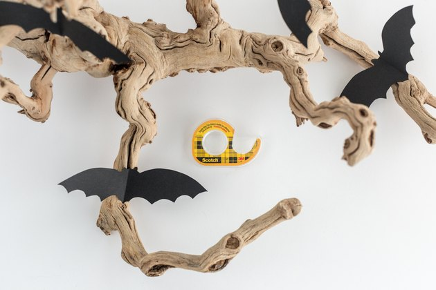 paper bat cut-outs stuck to a branch with tape
