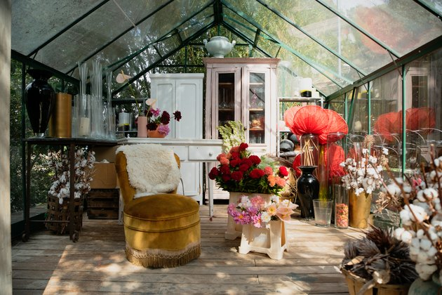 Greenhouse with mismatched, shabby chic furniture, plants and vases