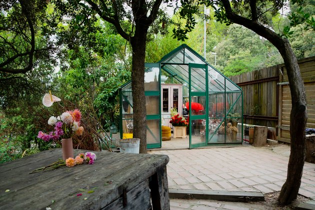 A green greenhouse in a backyard with a wood fence and wood dining table