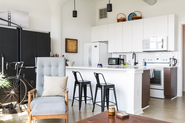 white, modern kitchen with black barstools and black cabinets
