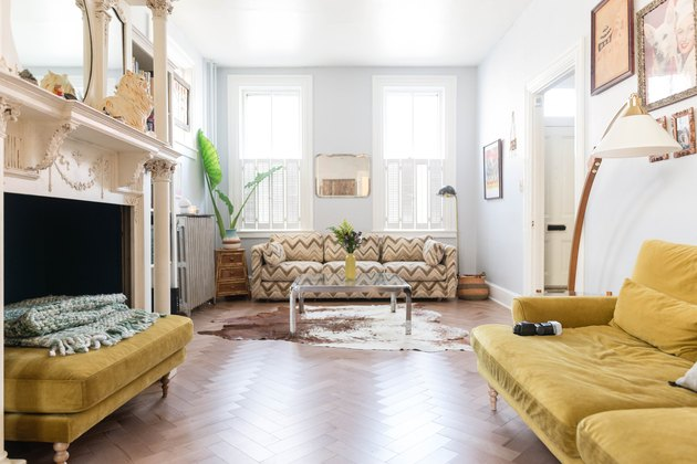 Yellow Room Ideas in Yellow couch, yellow cotton, zigzag pattern couch, chevron pattern wood floor, fireplace, white walls.