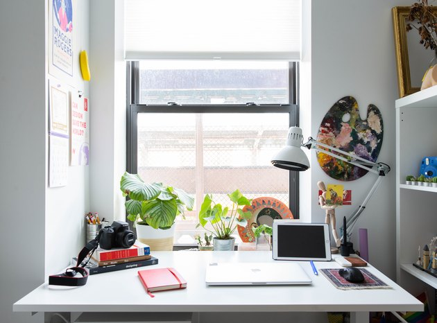 Desk with white desk lamp pushed up against open window