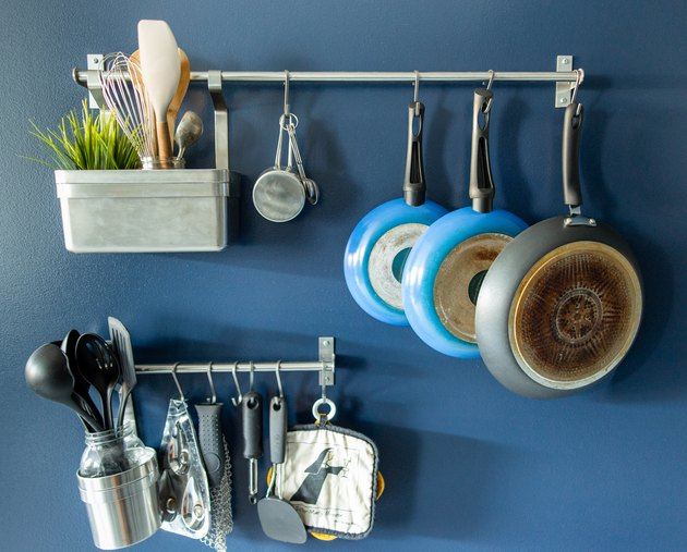 Hanging pots, pans, and utensils against royal blue wall