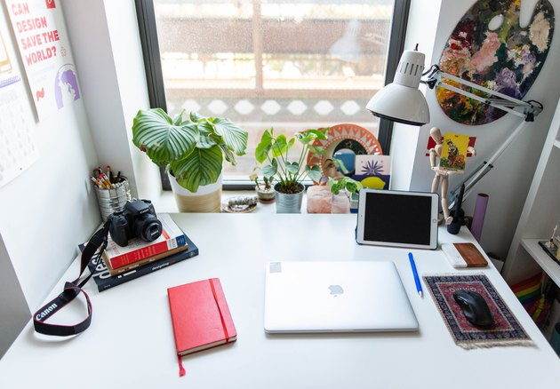 White desk with red notebook and closed laptop against window