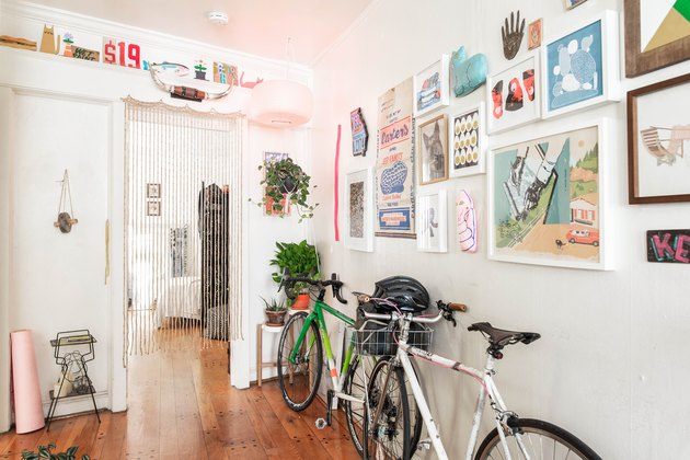 Apartment hallway with artwork and bikes leaning on them