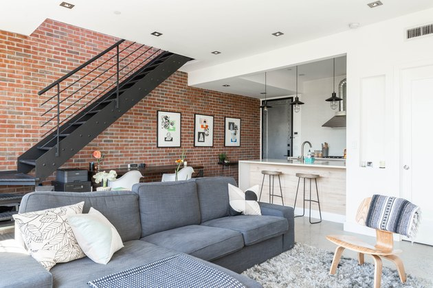 Black metal staircase against brick wall with wood table, white curved chairs, framed print, grey couch, white kitchen island