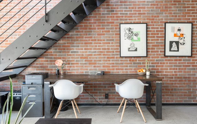 Black metal staircase against brick wall with wood table, white curved chairs, framed print, and small metal cabinet