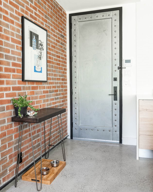 Entryway with brick wall, white wall, metal doo, small entryway table, and hung framed print