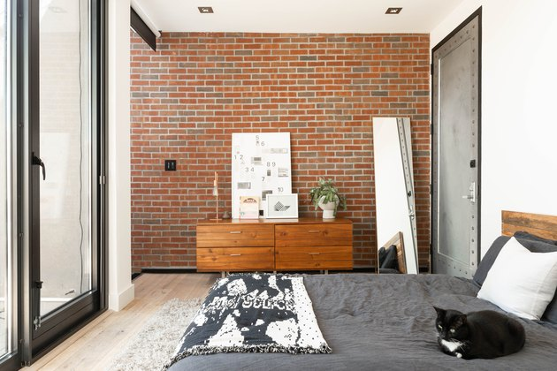 Contemporary bedroom with wood cabinets, lamp, plant, white diagram board, brick wall, full-length mirror, and black-and-white bed
