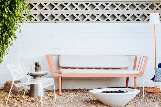 a pink bench with mid-century lines on gravel in front of a cone-shaped fire pit
