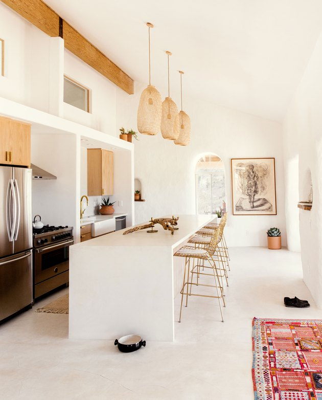 Desert kitchen with woven pendant lights and white kitchen island