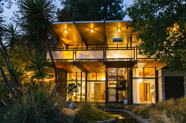 Large lit midcentury home with large windows and open balcony Home Exterior Ideas