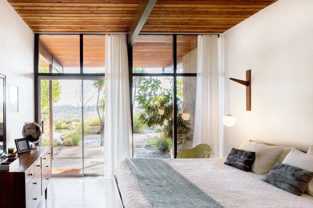Bedroom with floor to ceiling windows and white curtains