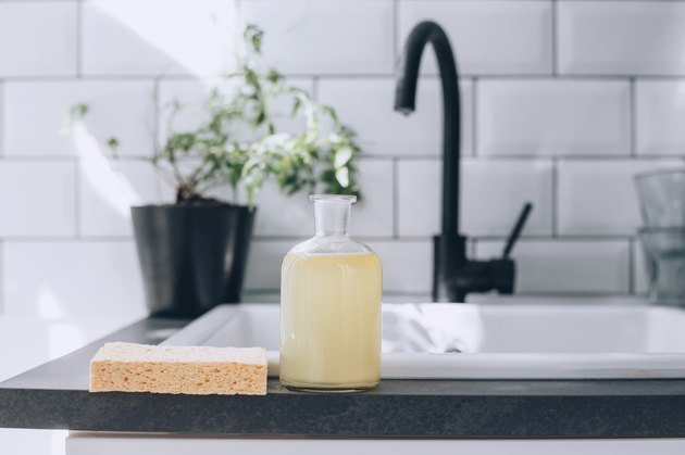 a glass bottle full of diy dish soap on a kitchen counter near the sink
