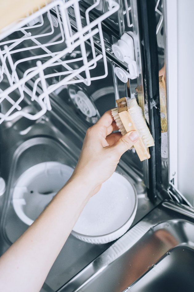 scrubbing the inside of a dishwasher
