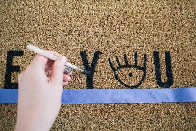 touching up the paint on a nearly finished painted doormat