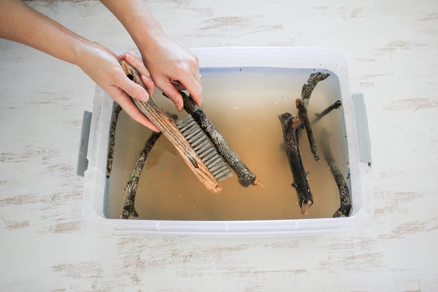 driftwood sticks are scrubbed in a basin with a stiff brush