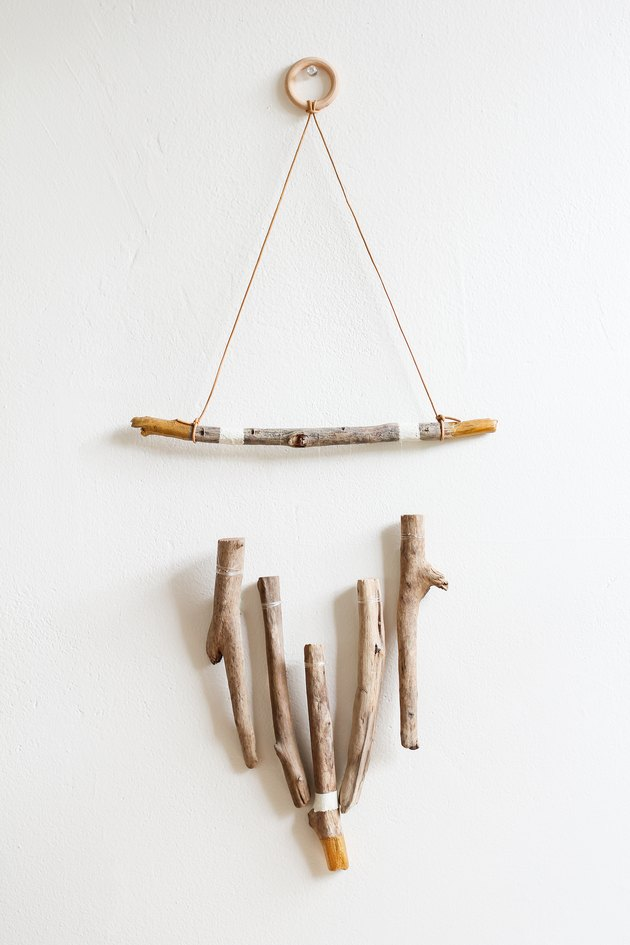 a wall hanging made of several vertical pieces of driftwood suspended from a horizontal one